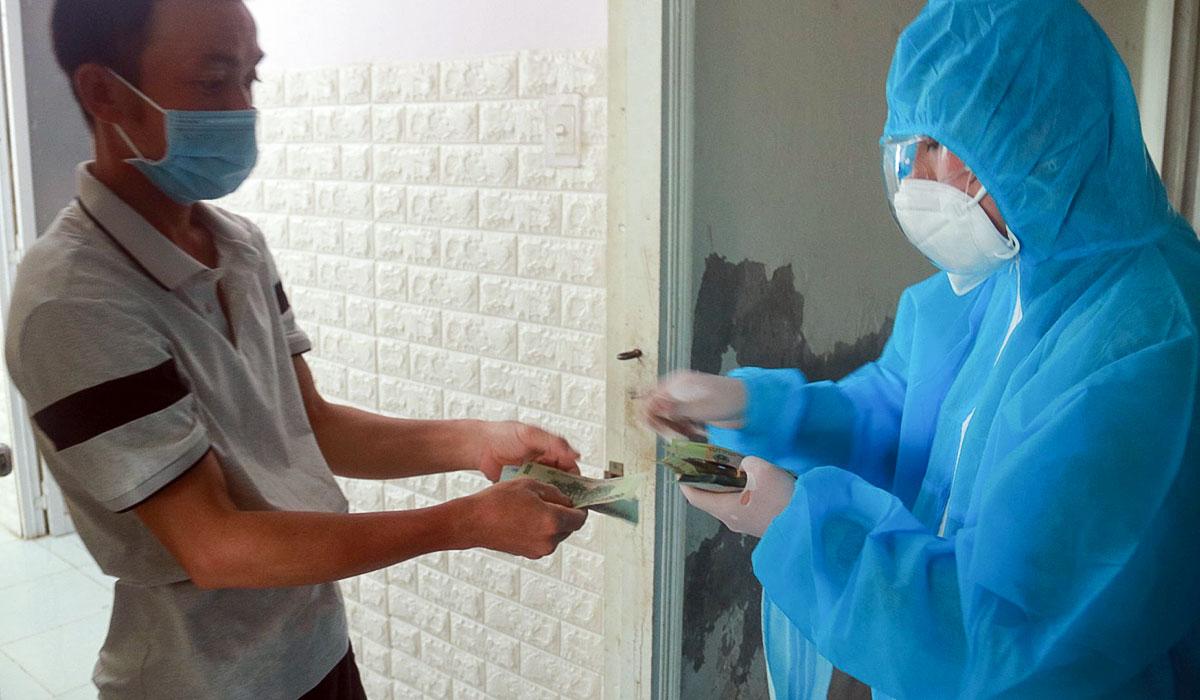 Đại diện tổ dân phố mang đồ bảo hộ khi đi phát tiền hỗ trợ cho người dân. Ảnh: Thành Đông.