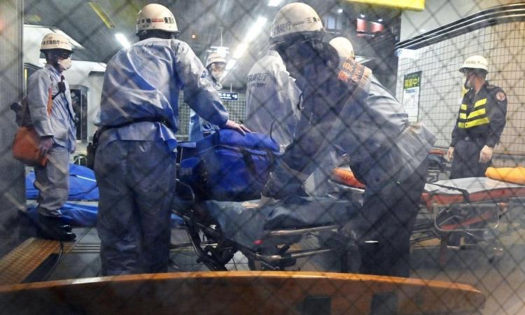 Lực lượng cứu hộ chuẩn bị cáng di chuyển nạn nhân sau vụ đâm dao ở ga Soshigaya Okura, Tokyo, Nhật Bản, hôm 6/8. Ảnh: AP.