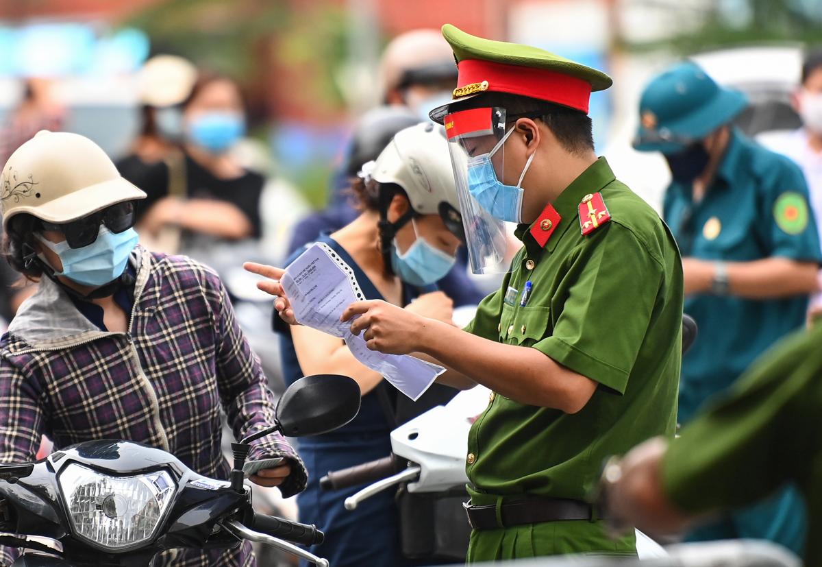 Công an kiểm tra giấy tờ của người đi đường hôm 28/7 trên phố Phạm Ngọc Thạch. Ảnh: Giang Huy.