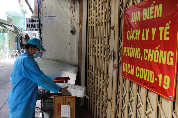 Tình nguyện viên tiếp tế nhu yếu phẩm cho từng nhà có người cách ly y tế trong khu phong toả trên đường Vườn Chuối, quận 3, ngày 30/7. Ảnh: Quỳnh Trần