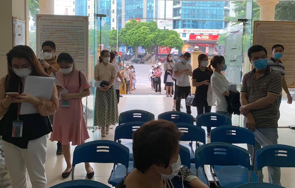 Người dân xếp hàng ở UBND phường Dịch Vọng Hậu để xin xác nhận giấy đi đường, chiều 9/8. Ảnh:Viết Tuân.