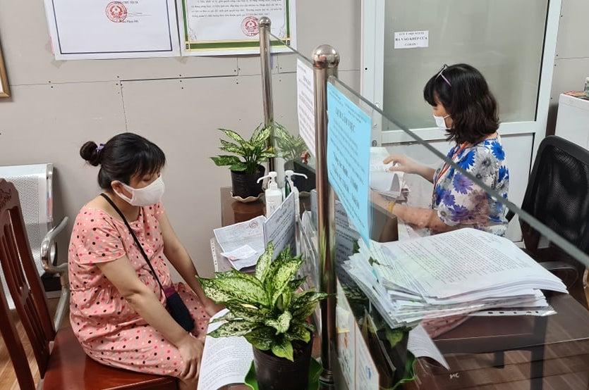 Chị Vũ Thị Thoa (trái) làm thủ tục xin xác nhận giấy đi đường ở phường Thượng Đình, quận Thanh Xuân, chiều 9/8. Ảnh: Tất Định