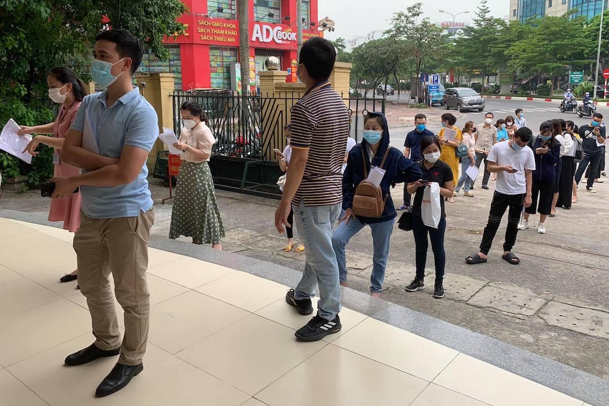 Người dân đến trụ sở phường Dịch Vọng Hậu đều phải mang theo hồ sơ để làm thủ tục xác nhận giấy đi đường. Ảnh: Viết Tuân