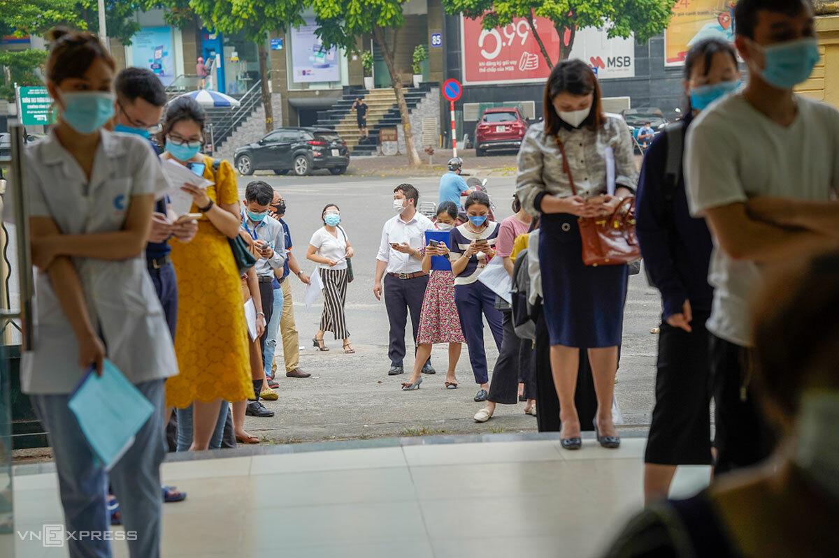 Người dân xếp hàng dài xin xác nhận giấy đi đường tại trụ sở phường Dịch Vọng Hậu, quận Cầu Giấy, Hà Nội, chiều 9/8. Ảnh: Phạm Chiểu