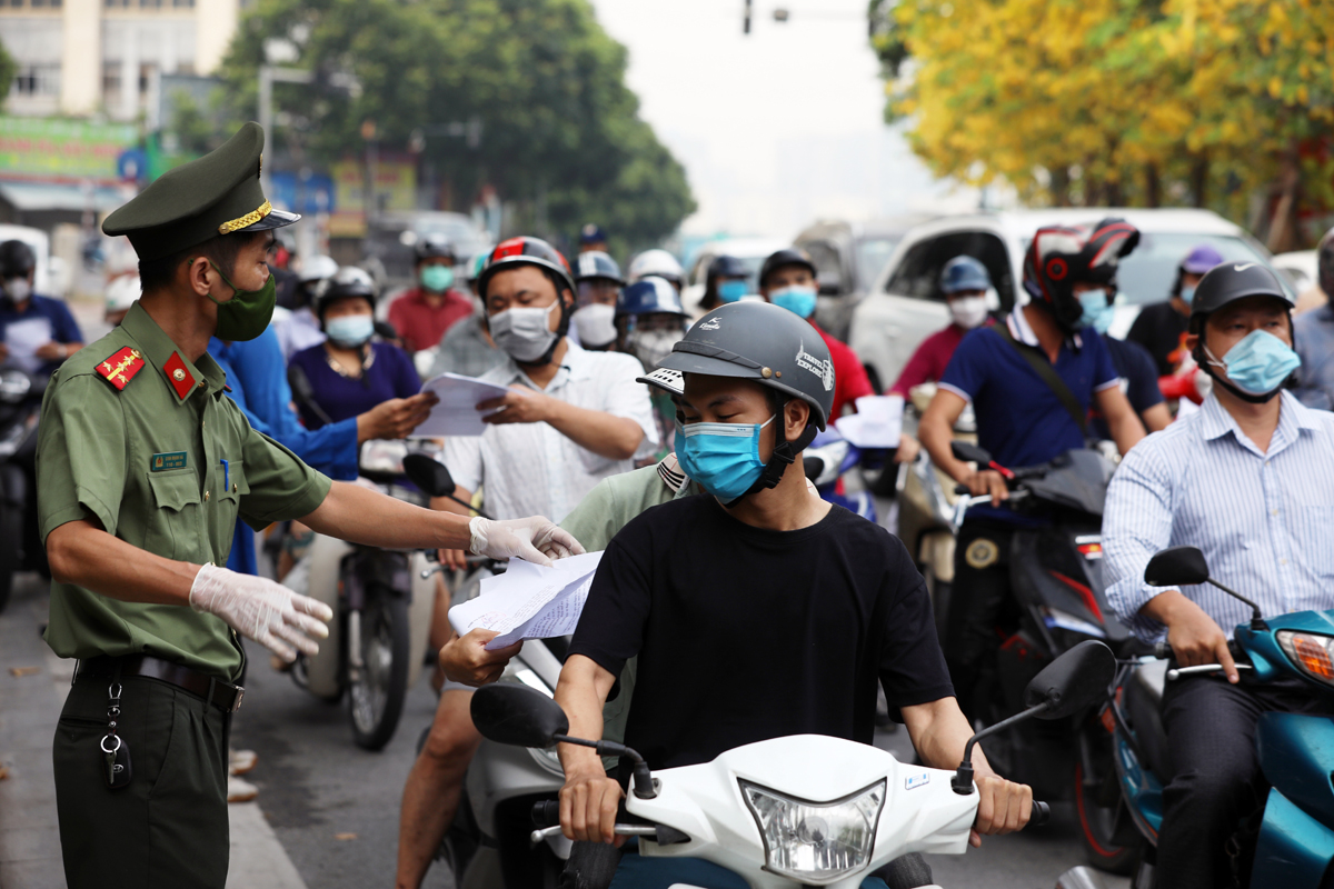 Lực lượng công an kiểm tra giấy tờ đi đường của người dân trên đường Nguyễn Chí Thanh, sáng 9/8. Ảnh: Ngọc Thành.