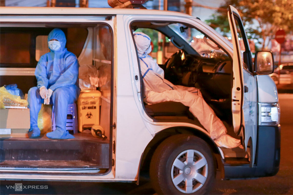 Kỹ thuật viên Phan Thị Loan (mặc đồ bảo hộ màu trắng), tranh thủ chợp mắt trên xe cứu thương sau buổi lấy mẫu kết thúc lúc 23h45, ngày 11/5. Ảnh: Nguyễn Đông.