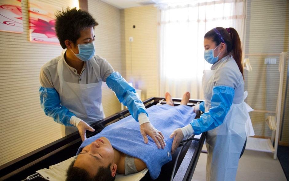 Các học viên đóng vai khách hàng đã khuất và chuyên viên xử lý tử thi tại một trường dạy nghề ở Chiết Giang, Trung Quốc vào năm 2012. Ảnh: Xinhua.