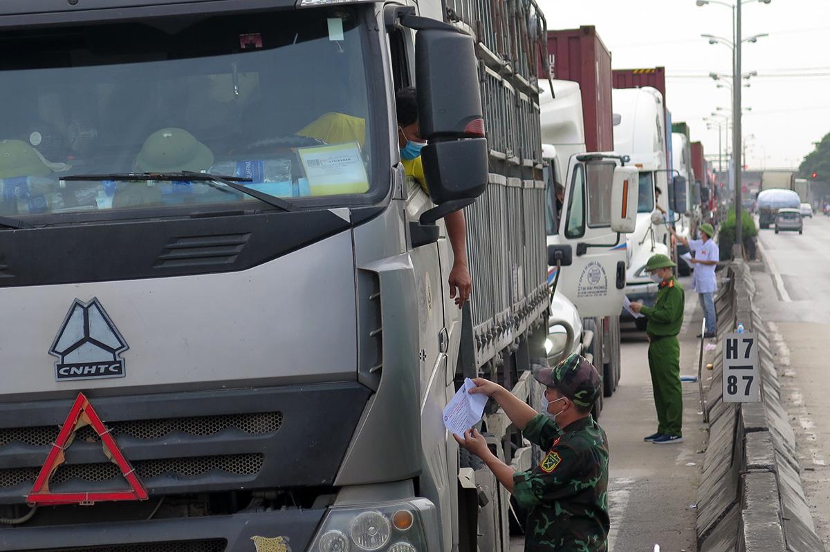 Tất cả các phương tiện vận tải hàng hóa vào Hải Phòng qua chốt phụ trên quốc lộ 5 đặt tại vị trí trạm thu phí cũ thuộc địa bàn xã Nam Sơn, huyện An Dương vẫn bị dừng xe kiểm soát mặc dù các xe đều đã có mã QR, lái xe có giấy xét nghiệm âm tính PCR. Ảnh: Giang Chinh