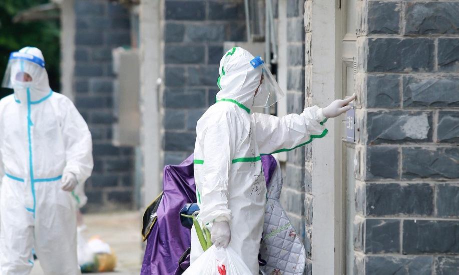Tình nguyện viên mang nhu yếu phẩm đến các gia đình bị phong tỏa ở Dương Châu hôm 6/8. Ảnh: AFP.