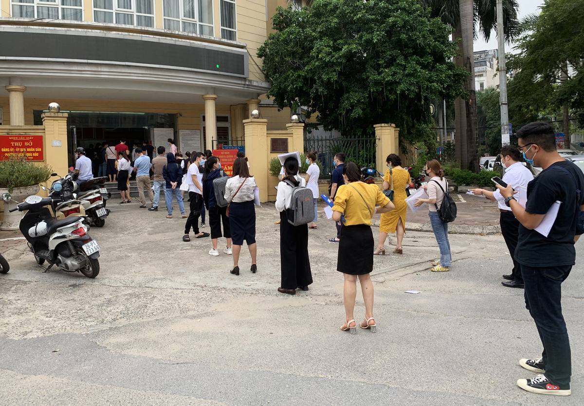 Người dân xếp hàng xin xác nhận giấy đi đường tại trụ sở phường Dịch Vọng Hậu, chiều 9/8. Ảnh: Viết Tuân.
