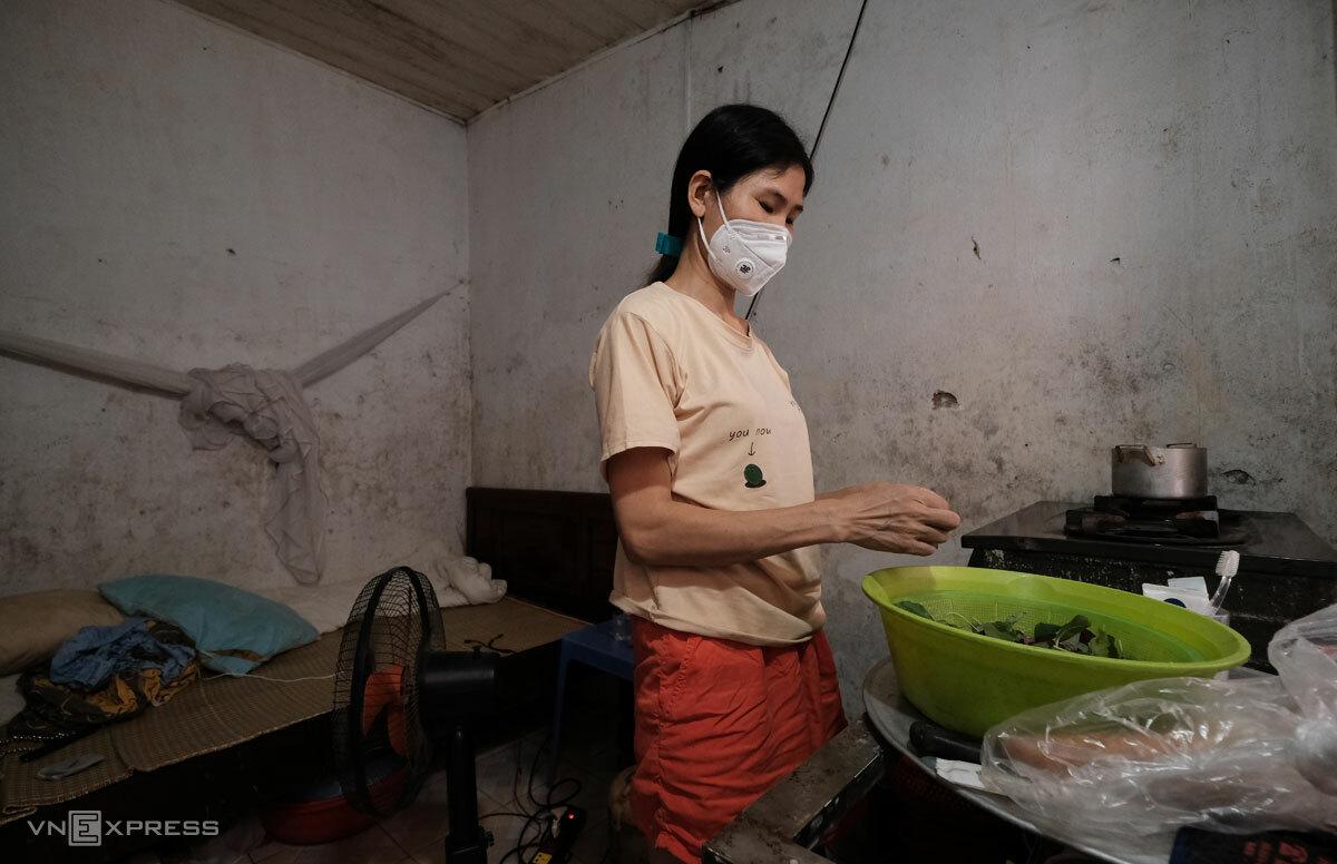 Chị Thắm chuẩn bị cơm trưa với một mớ rau dền chia đôi cho hai bữa mỗi ngày, tháng 8/2021. Ảnh: Hồng Chiêu