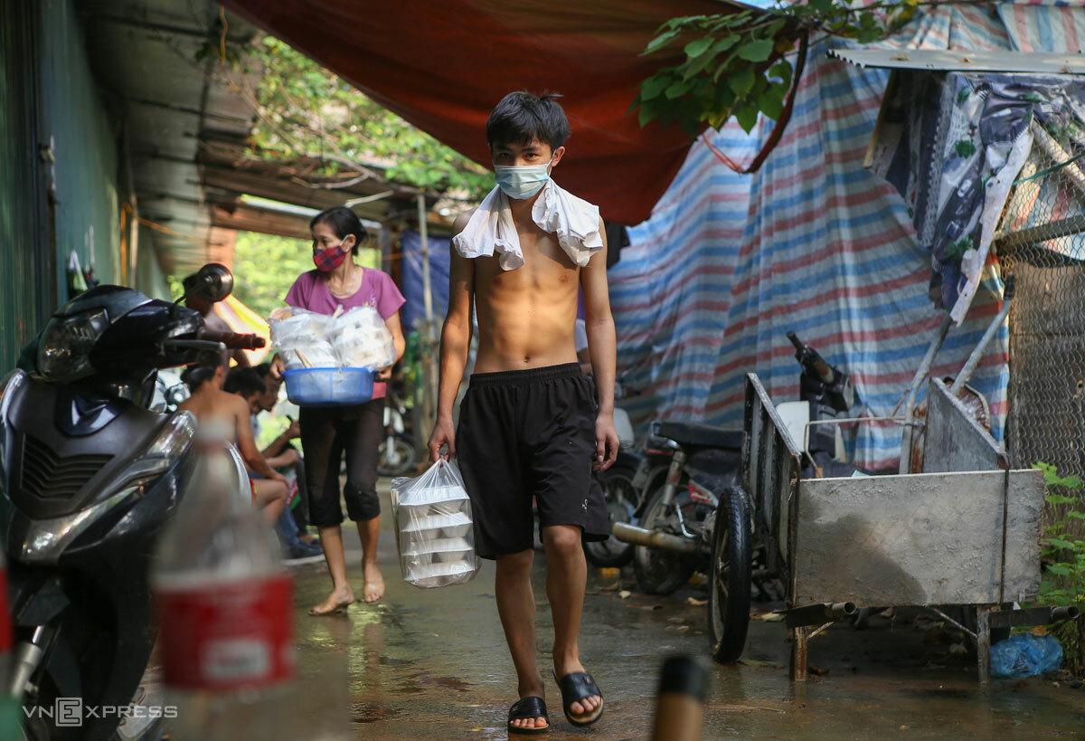 Công nhân xây dựng mang cơm được hỗ trợ miễn phí về phòng, tháng 8/2021. Ảnh: Hồng Chiêu