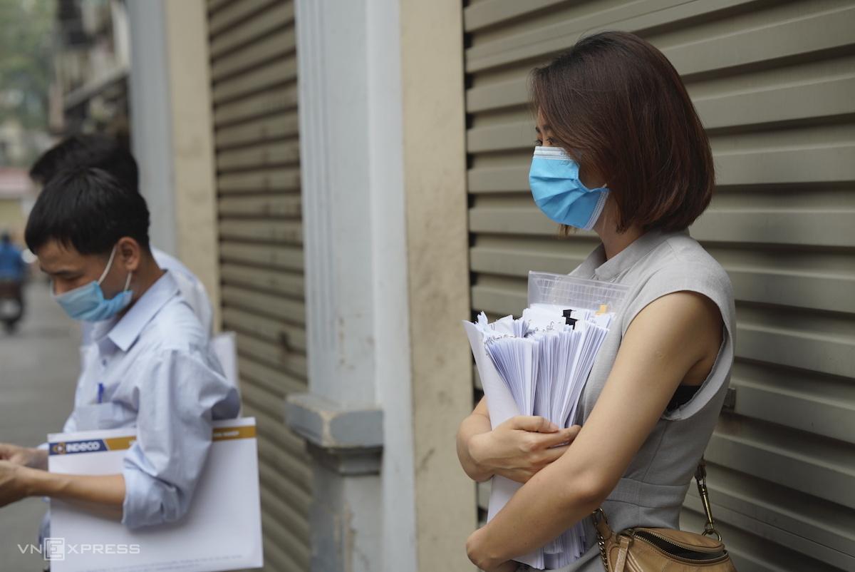 Chị Nguyễn Thu Giang cầm tập hồ sơ chờ làm thủ tục xác nhận giấy đi đường. Ảnh: Phạm Chiểu