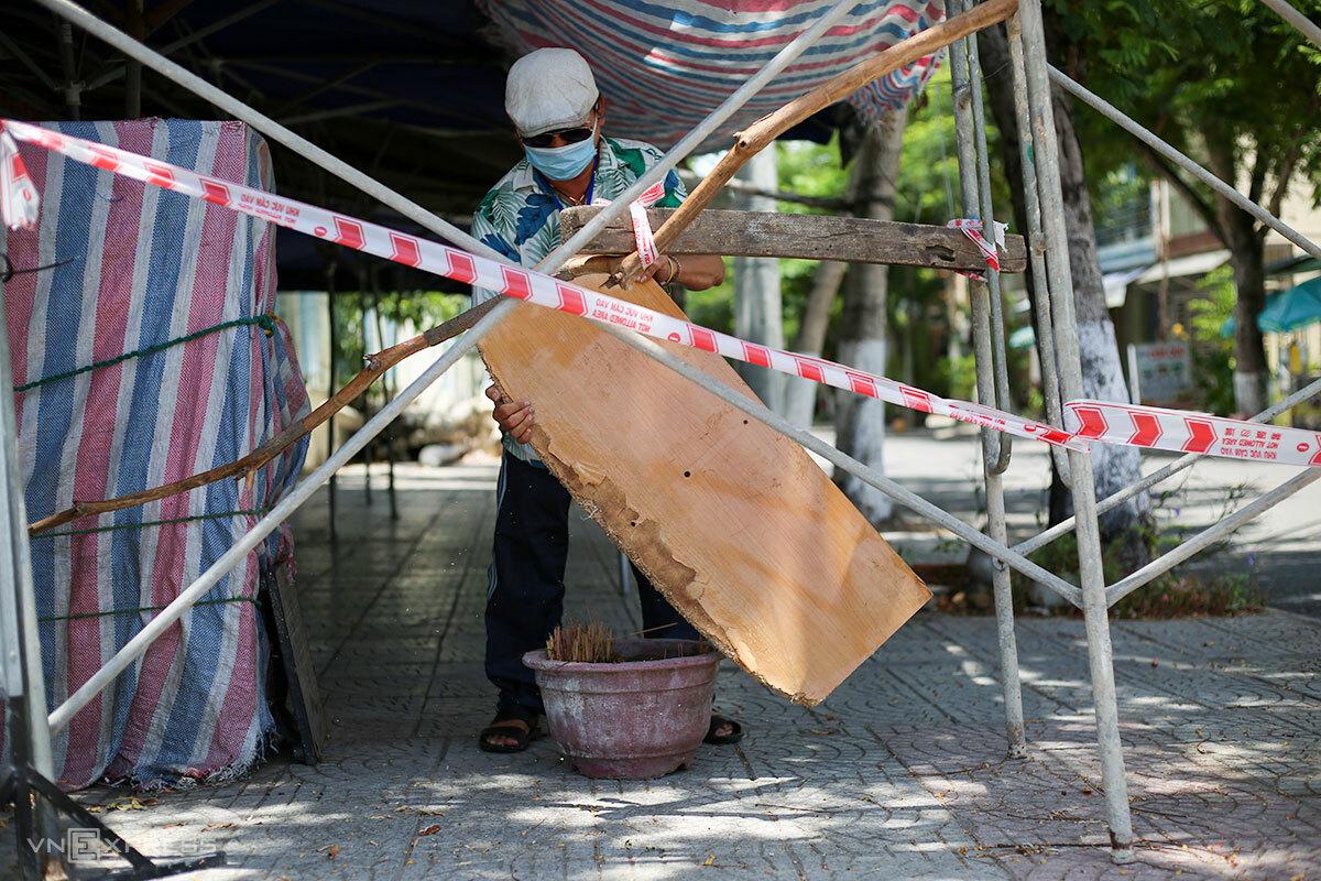 Một thành viên Tổ Covid cộng đồng ở quận Sơn Trà dựng chướng ngại vật tại một chốt cứng, ngăn người qua lại, trưa 3/8. Ảnh: Nguyễn Đông.