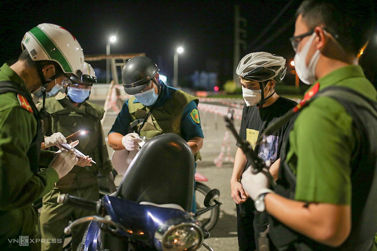 Công an phường An Hải Bắc (quận Sơn Trà) kiểm tra một người ra đường lúc 23h40 ngày 4/8. Ảnh: Nguyễn Đông.