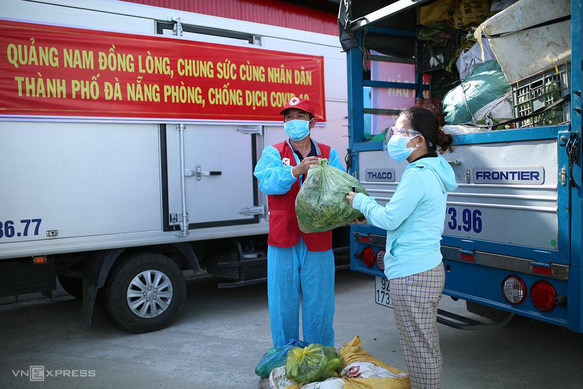 Ông Phan Xuân Chiến, Chủ tịch Hội chữ thập đỏ huyện Đại Lộc trao tượng trưng rau xanh cho đại diện quận Sơn Trà, sáng 10/8. Ảnh: Nguyễn Đông.