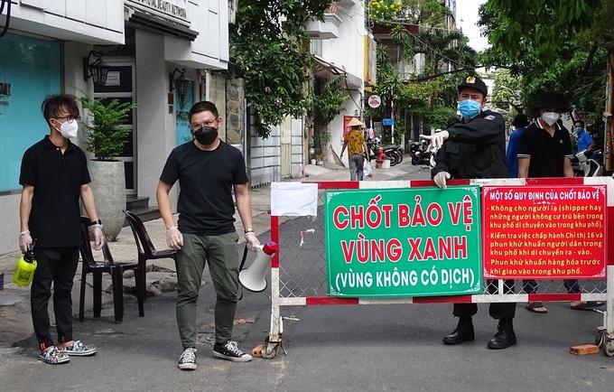 Lực lượng tình nguyện viên và công an kiểm soát ra vào tại cổng chính cư xá Đô Thành ngày 24/7. Ảnh: Hà An.