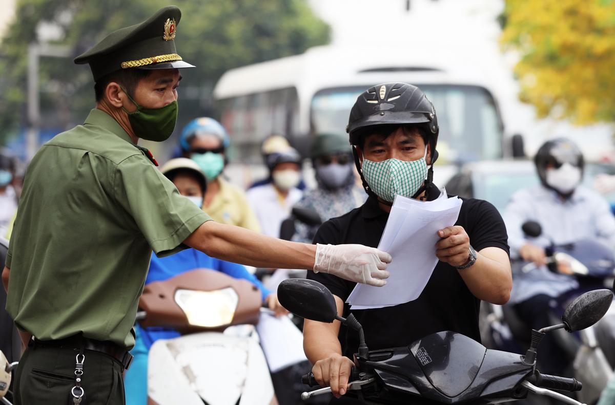 Công an kiểm tra giấy đi đường của người dân trên đường Nguyễn Chí Thanh, sáng 9/8. Ảnh: Ngọc Thành.