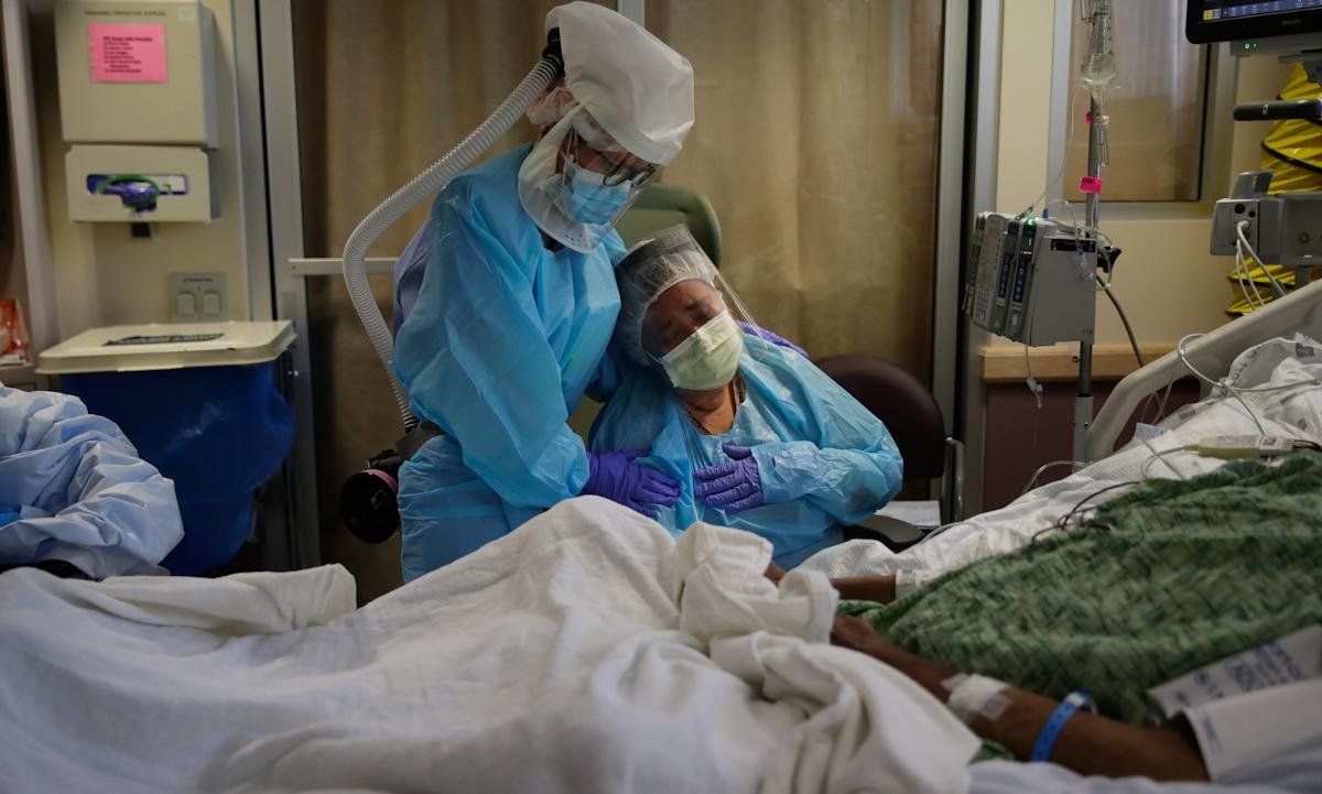 Y tá an ủi một người phụ nữ đau lòng nhìn cảnh chồng hấp hối vì Covid-19 tại Fullerton, California, Mỹ hồi tháng 7/2020. Ảnh: AP.