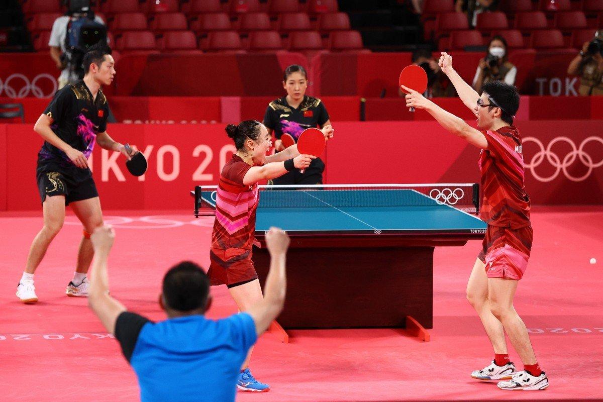 Cặp VĐV Nhật Bản Mima Ito và Jun Mizutani ăn mừng chiến thắng trước đội bóng bàn Trung Quốc tại Olympic Tokyo ngày 26/7. Ảnh: Reuters.