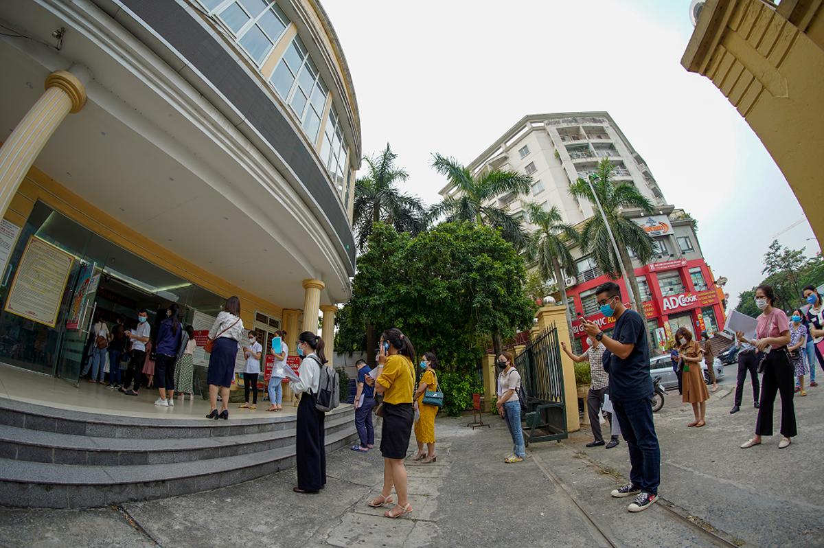 Người dân xếp hàng dài đợi làm thủ tục xác nhận giấy đi đường ở phường Dịch Vọng Hậu (Cầu Giấy), chiều 9/8. Ảnh: Phạm Chiểu.