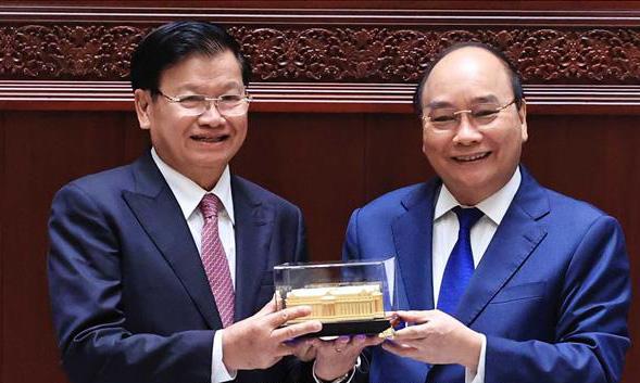 Chủ tịch nước Nguyễn Xuân Phúc (phải) trao mô hình Nhà Quốc hội mới cho Tổng Bí thư, Chủ tịch nước Lào Thongloun Sisoulith tại Vientian hôm nay. Ảnh: TTXVN.