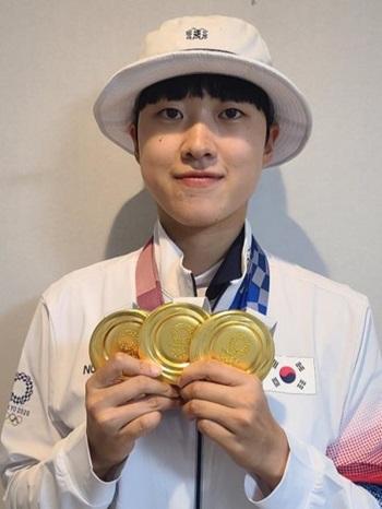 Cung thủ Hàn Quốc An San khoe ba huy chương vàng mà cô giành được tại Olympic 2020. Ảnh: Yonhap.