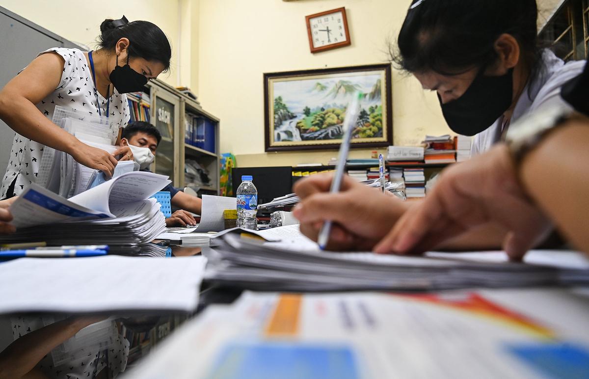 Người dân làm thủ tục xác nhận giấy đi đường tại trụ sở phường Vĩnh Tuy (Hai Bà Trưng) lúc 21h30 ngày 9/8. Ảnh: Giang Huy.