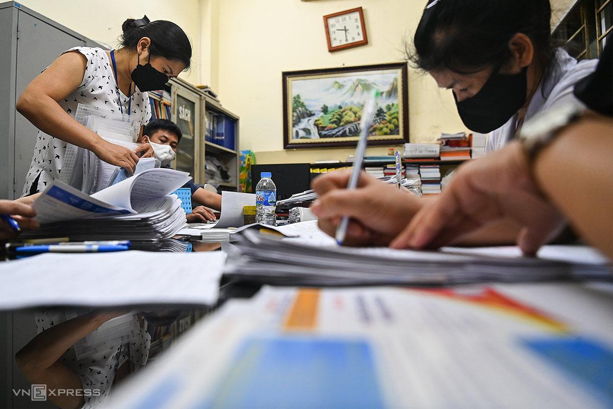 Cán bộ phường Vĩnh Tuy rà soát hồ sơ để xác nhận giấy đi đường theo mẫu mới cho người dân lúc 21h ngày 9/8. Ảnh: Giang Huy.