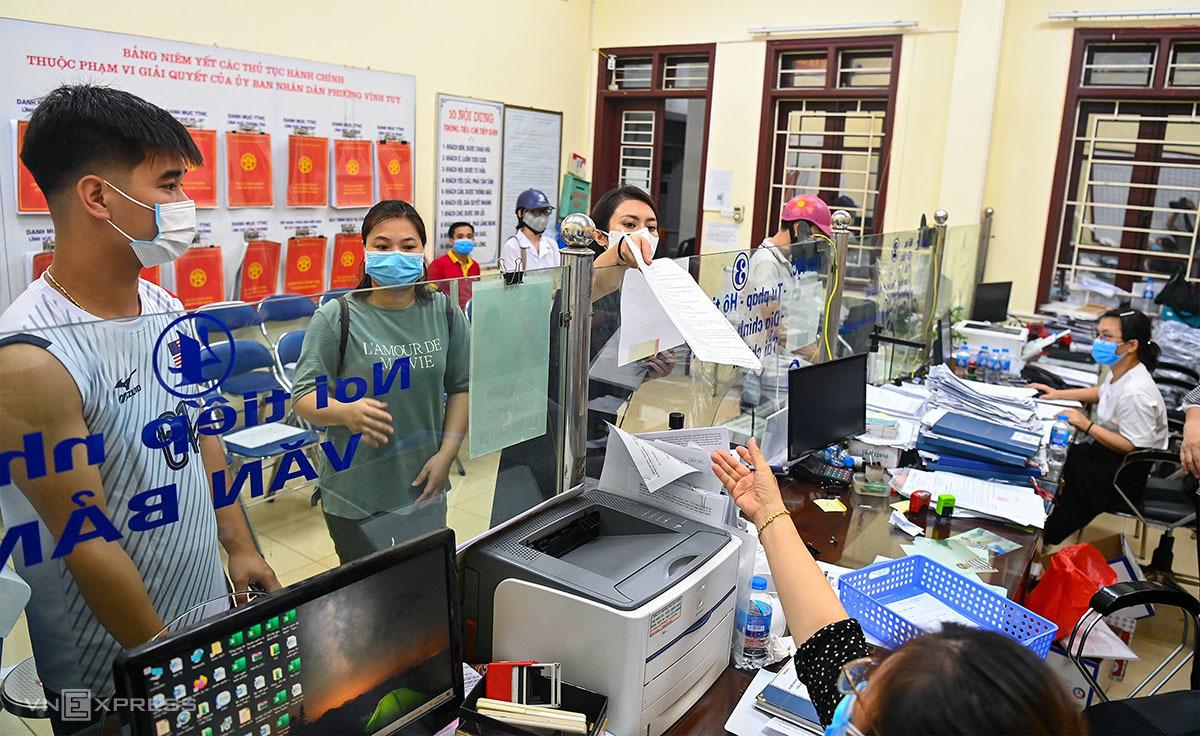 Người dân làm thủ tục xin xác nhận giấy đi đường  tại trụ sở UBND phường Vĩnh Tuy lúc 22h ngày 9/8. Ảnh: Giang Huy.