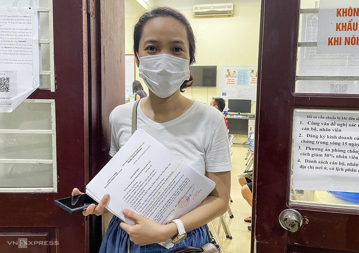 Chị Nguyễn Hải Yến, 36 tuổi, quản lý một công ty may mặc xin xác nhận giấy đi đường cho nhân viên tối 9/8. Ảnh: Giang Huy.