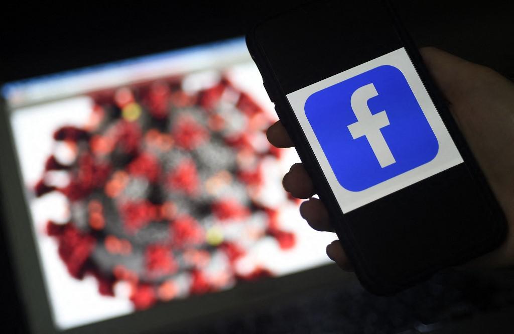 Logo của Facebook trên màn hình điện thoại di động, phía sau là hình nền minh họa nCoV tại Arlington, bang Virginia, Mỹ, ngày 25/3/2020. Ảnh: AFP.