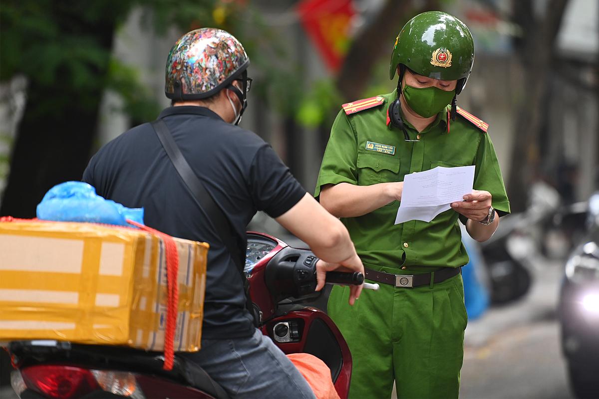 Công an kiểm tra giấy đi đường của người dân ở Hà Nội. Ảnh: Giang Huy