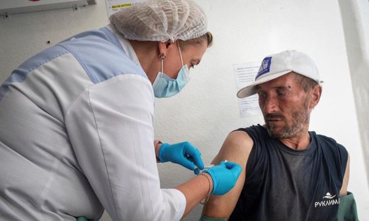 Một người đàn ông vô gia cư được tiêm vaccine Covid-19 tại thành phố Saint Petersburg, Nga hôm 4/8. Ảnh: Reuters.