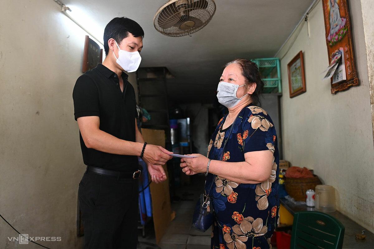 Gia đình khó khăn ở phường Hàng Bồ, quận Hoàn Kiếm nhận hỗ trợ 1,5 triệu đồng, hôm 7/8. Ảnh: Giang Huy