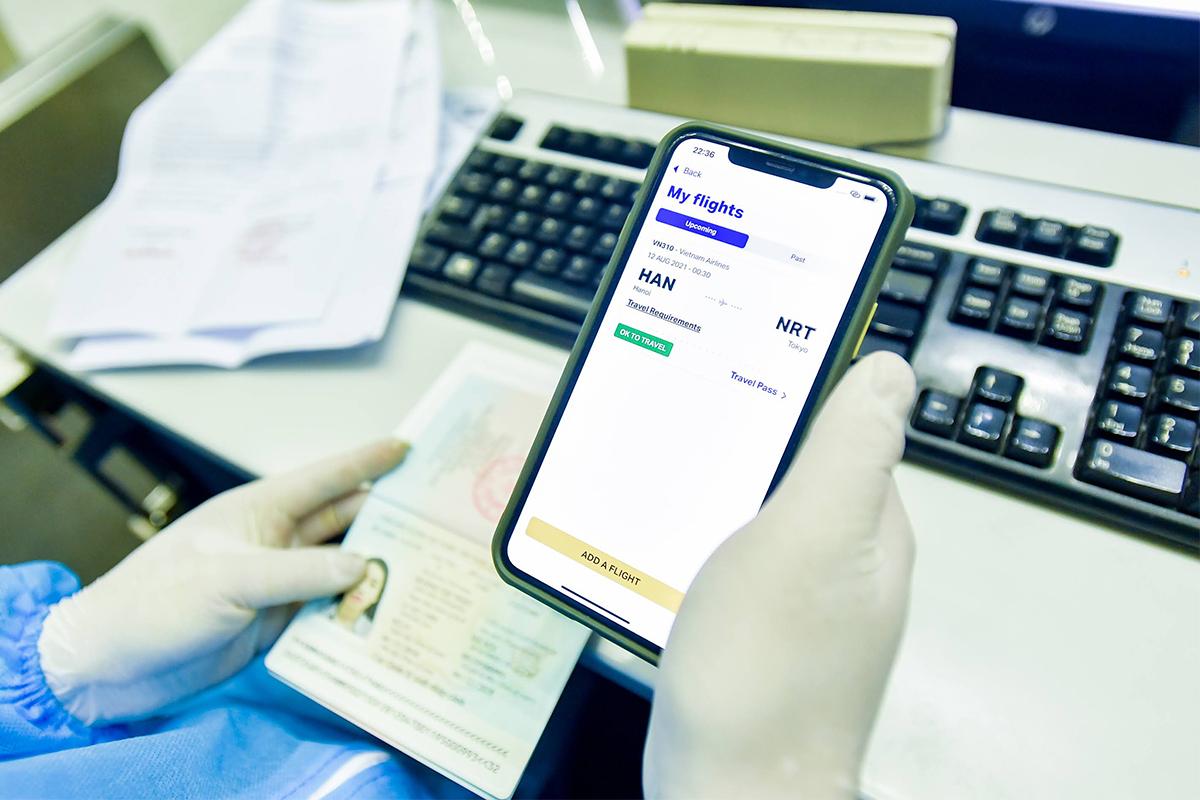 Tại quầy check-in sân bay, hành khách xuất trình hộ chiếu, kết quả xét nghiệm Covid-19 trên ứng dụng IATA Travel Pass cùng với kết quả xét nghiệm bản cứng. Ảnh: VNA.