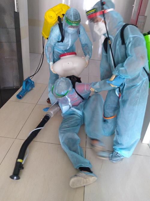 Bình phun nặng cộng với sàn nhà trơn khiến một thành viên trong đội của Nguyên bị trượt chân khi làm nhiệm vụ. Ảnh: NVCC.
