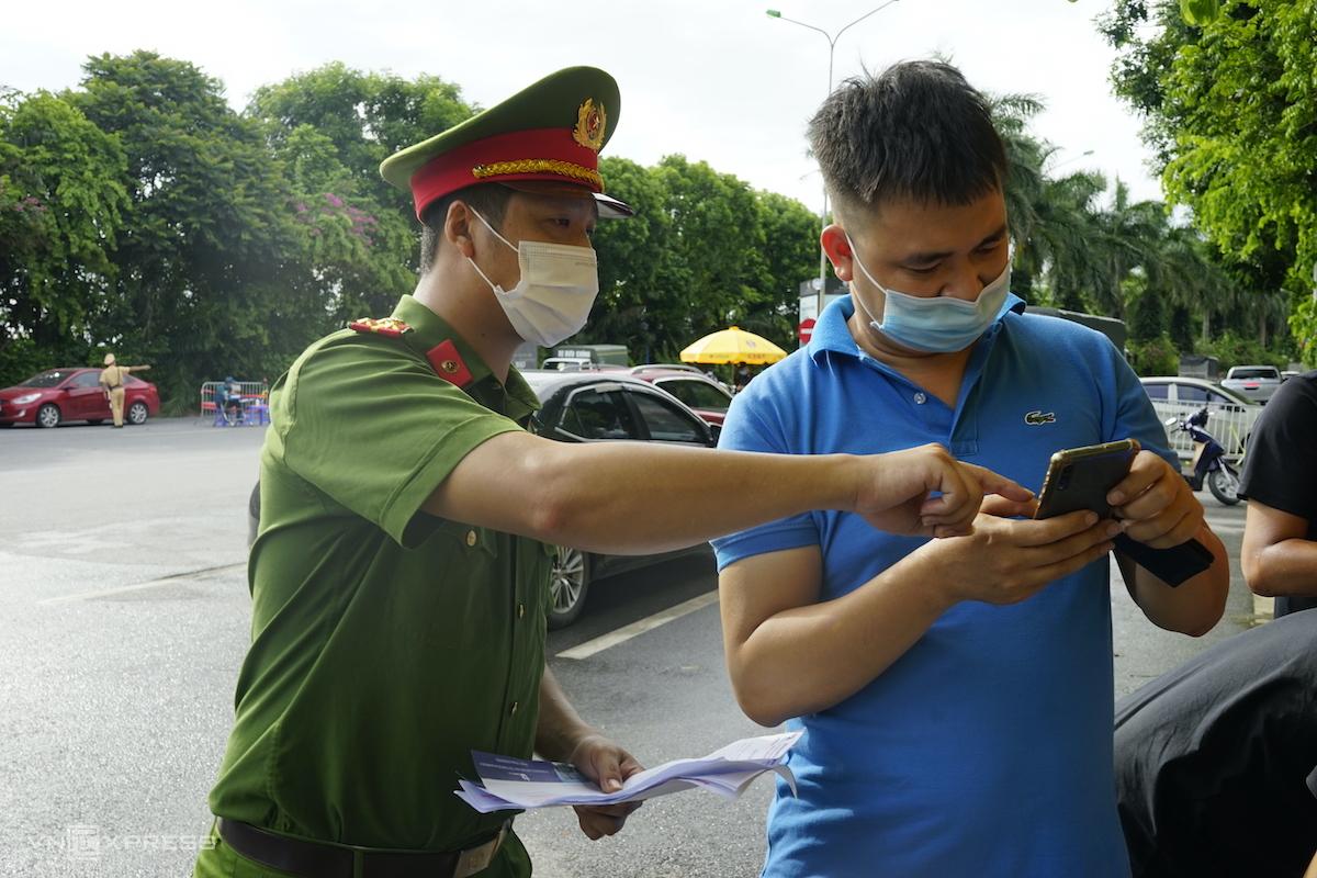 Cảnh sát hướng dẫn cách thức khai báo tại chốt số 7, chiều 13/8. Ảnh: Gia Chính