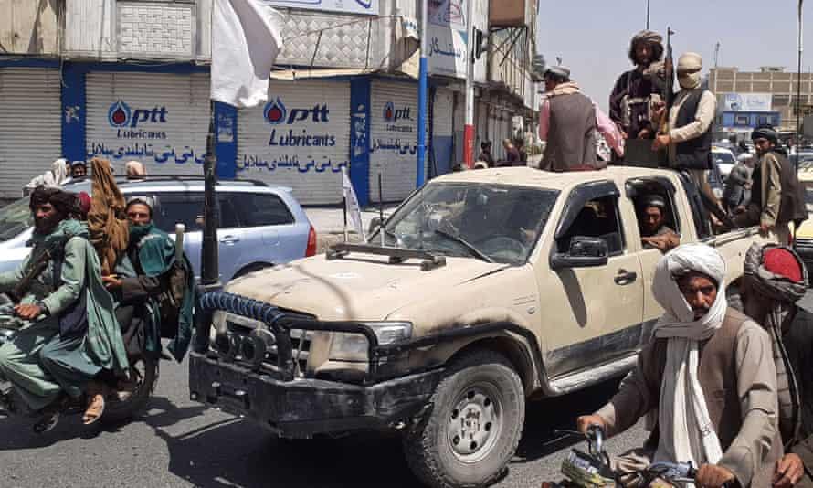 Phiến quân Taliban lái xe của quân đội Afghanistan qua một con phố ở Kandahar hôm 6/8. Ảnh: AFP