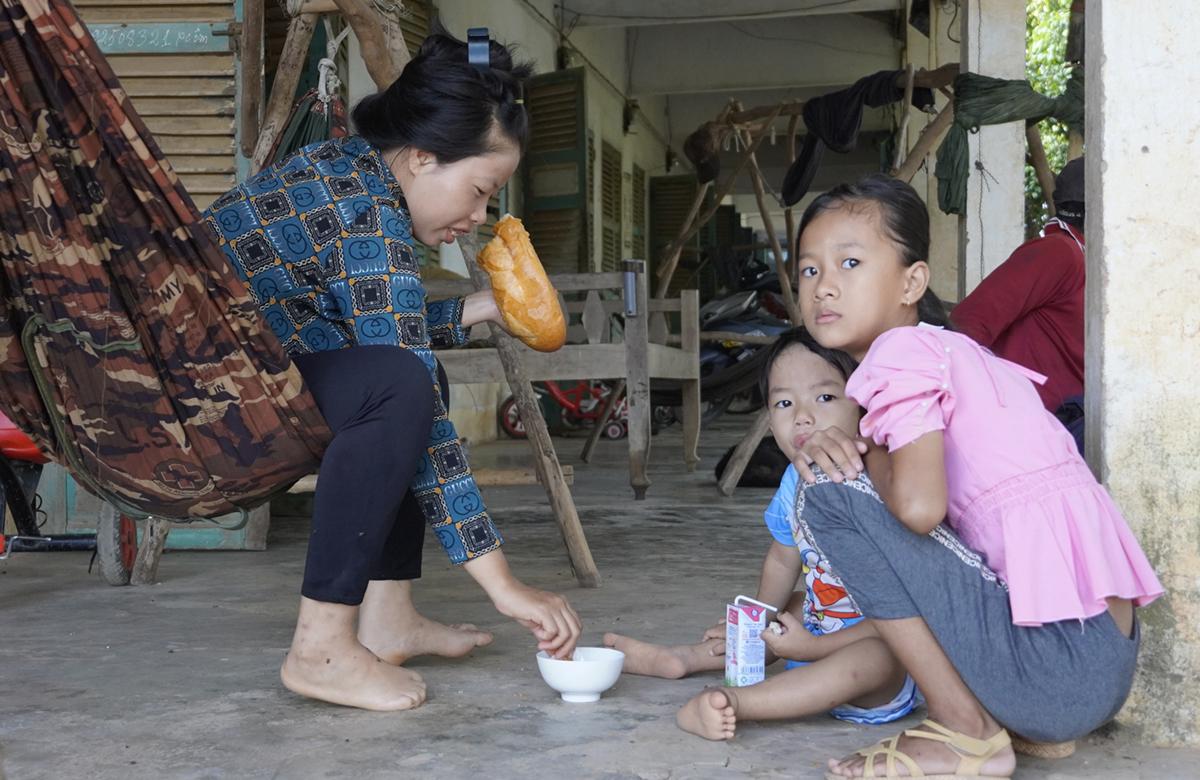 Chị Hà Thị Thi cùng con trai và cháu ăn bánh mì trước khi vào xưởng làm việc. Ảnh: Hoàng Nam