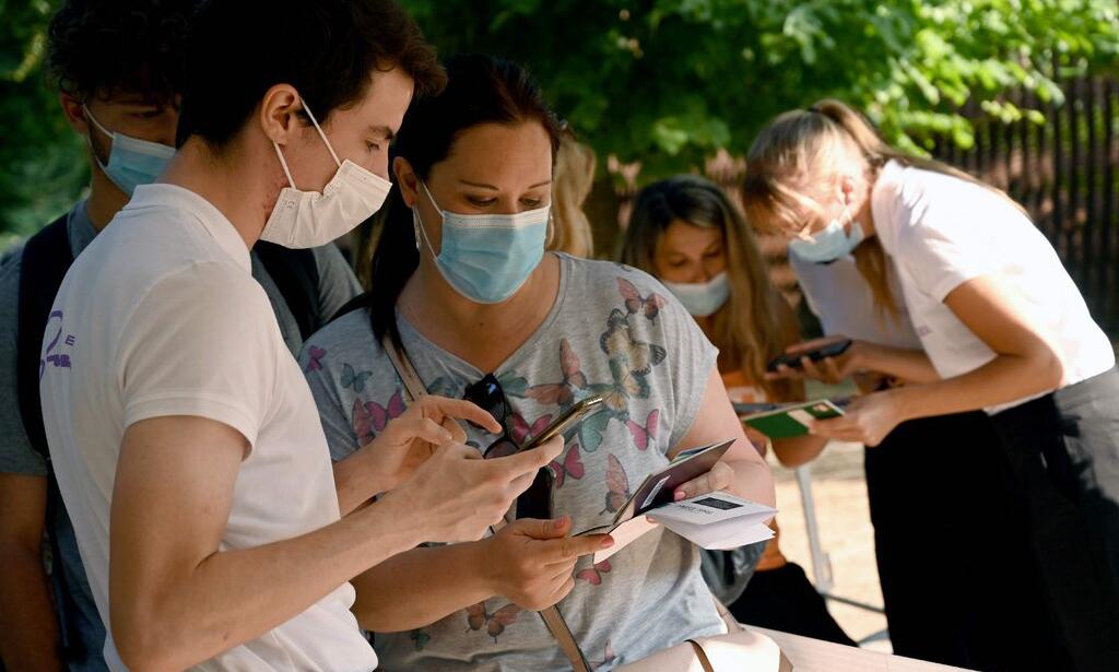Nhân viên  tháp Eiffel kiểm tra hộ chiếu vaccine của khách tại Paris, Pháp hôm 21/7. Ảnh: AFP.