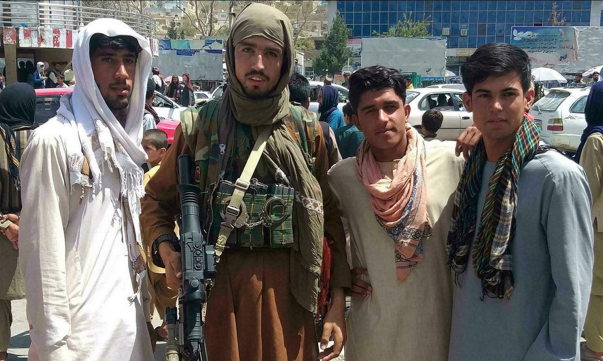 Tay súng Taliban trang bị vũ khí phương Tây và người dân thành phố Pul-e-Khumri hôm 11/8. Ảnh: AFP.