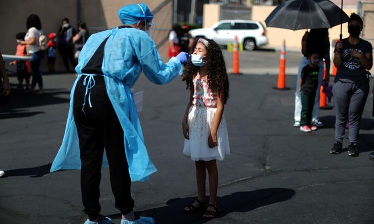 Nhân viên y tế lấy mẫu xét nghiệm Covid-19 cho một em nhỏ tại thành phố Los Angeles, bang California, ngày 12/8. Ảnh: Reuters.