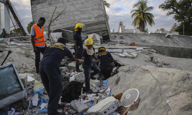 Lính cứu hỏa tìm kiếm người còn sống sót bên trong tòa nhà bị tàn phá ở Les Cayes, Haiti, hôm 15/8. Ảnh: AP.