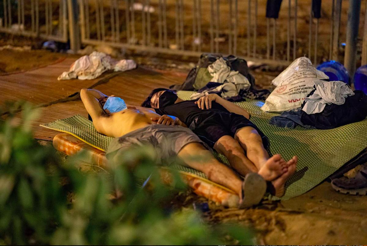 Một số lao động ngoại tỉnh ngủ dưới gầm đường vành đại 3 trên cao (đoạn bến xe Mỹ Đình) đêm 13/8. Những người này sau đó được hỗ trợ sắp xếp nơi ở tạm. Ảnh: Phạm Chiểu.