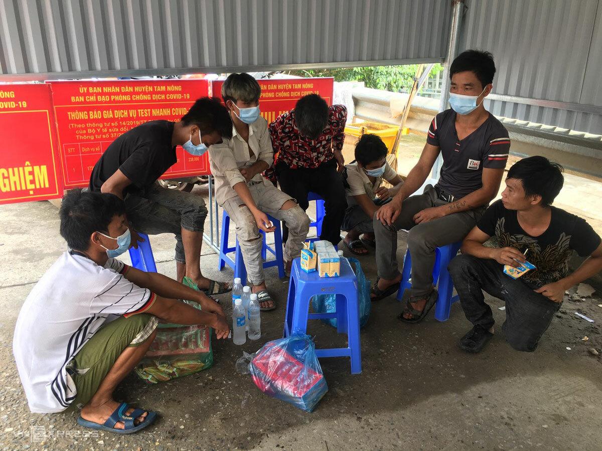 Nhóm lao động được hỗ trợ đồ ăn, ngồi đợi kết quả test nhanh Covid-19 tại chốt kiểm dịch huyện Tam Nông, sáng 17/8. Ảnh: Hồng Chiêu