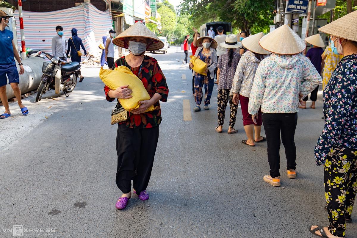 Người khó khăn nhận gạo từ thiện trên đường Mỹ Đình, hôm 7/8. Ảnh: Tùng Đinh