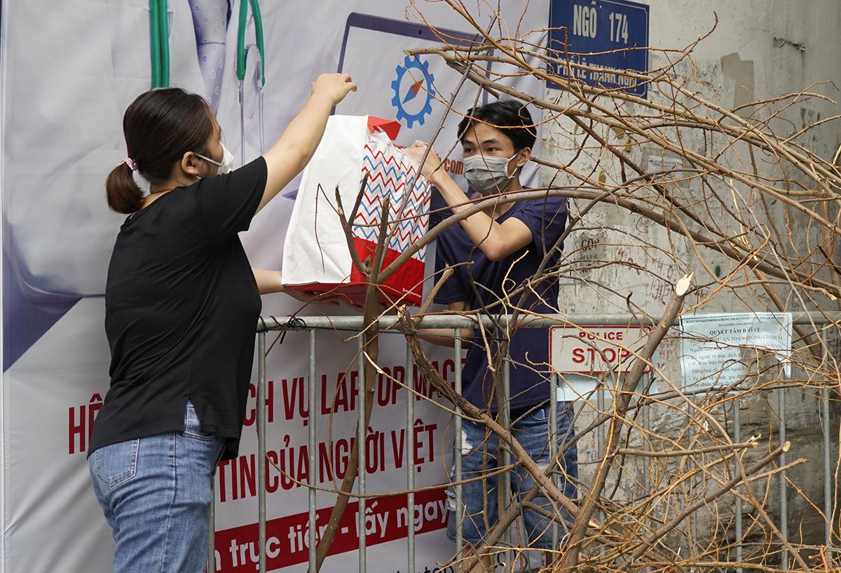 Sinh viên Đại học Bách khoa Hà Nội nhận nhu yếu phẩm do trường hỗ trợ qua chốt kiểm dịch cứng ở ngõ 174 phố Lê Thanh Nghị. Ảnh: HUST.