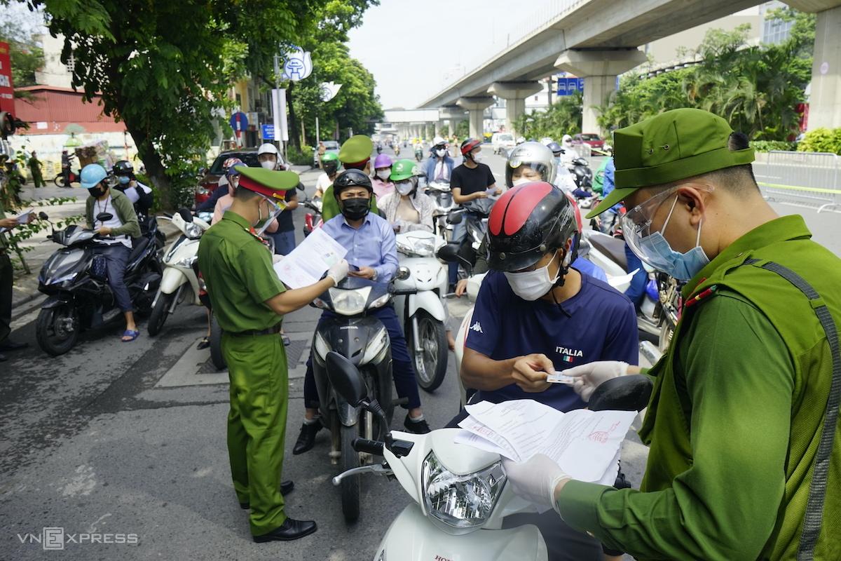Người dân xuất trình giấy đi đường tại chốt Nguyễn Trãi, sáng 17/8. Ảnh: Gia Chính
