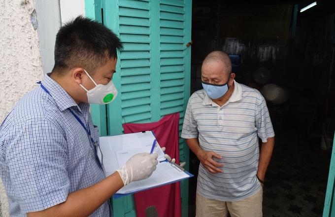 Ông Vương Chí Tài (phải), 72 tuổi, làm nghề bán vé số, ở phường Đa Kao, quận 1, nhận tiền hỗ trợ đợt một, trưa 12/7. Ảnh: Hà An